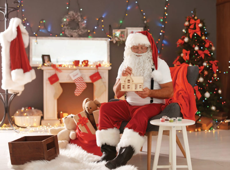 man in santa outfit in front of fireplace and Christmas tree